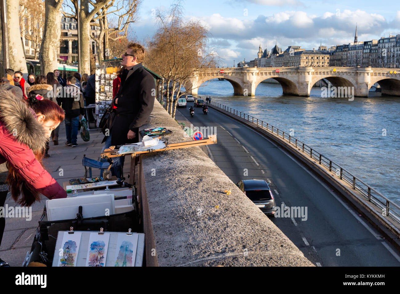 PARIS - Jan 2, 2014: Art and book sellers on a busy street with a view of the Seine River below. A shopper looks - Stock Image