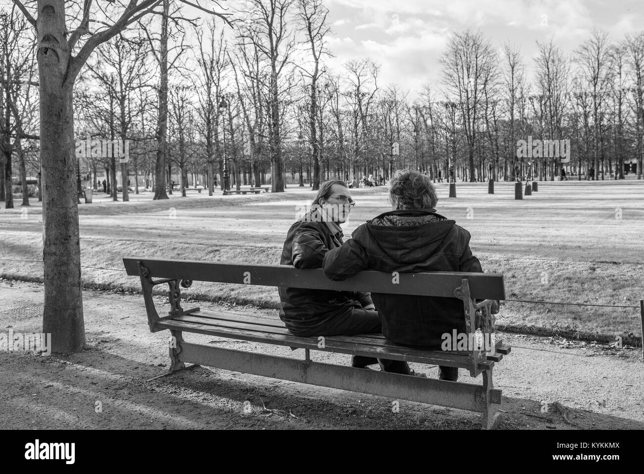 PARIS-Jan.3, 2014: Two men sit on a park bench talking on a winter day. Black and white. - Stock Image