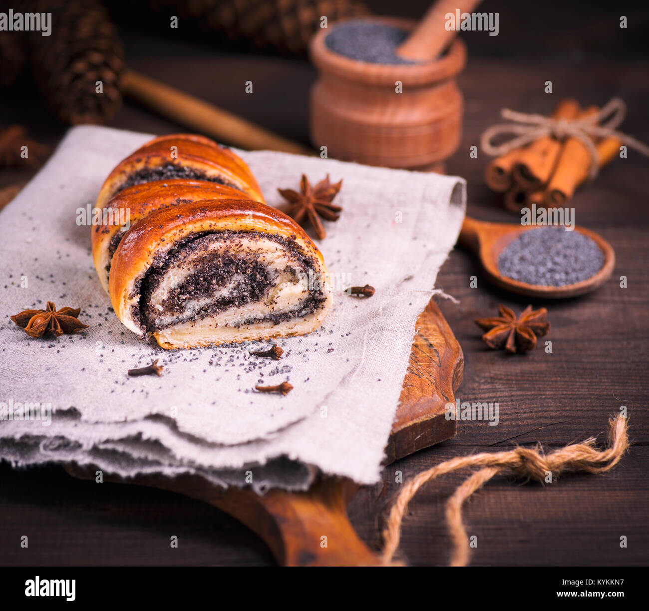 poppy roll on a gray linen napkin and poppy seeds in a wooden spoon, close up - Stock Image