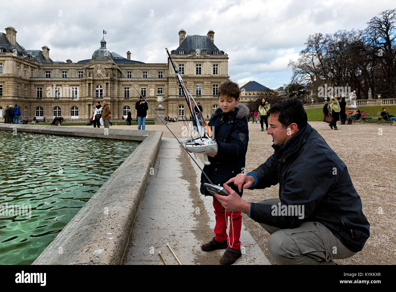 PARIS, FRANCE - JAN 4, 2014: An unidentified child learns how to sail a model boat at the Jardin du Luxembourg, Stock Photo
