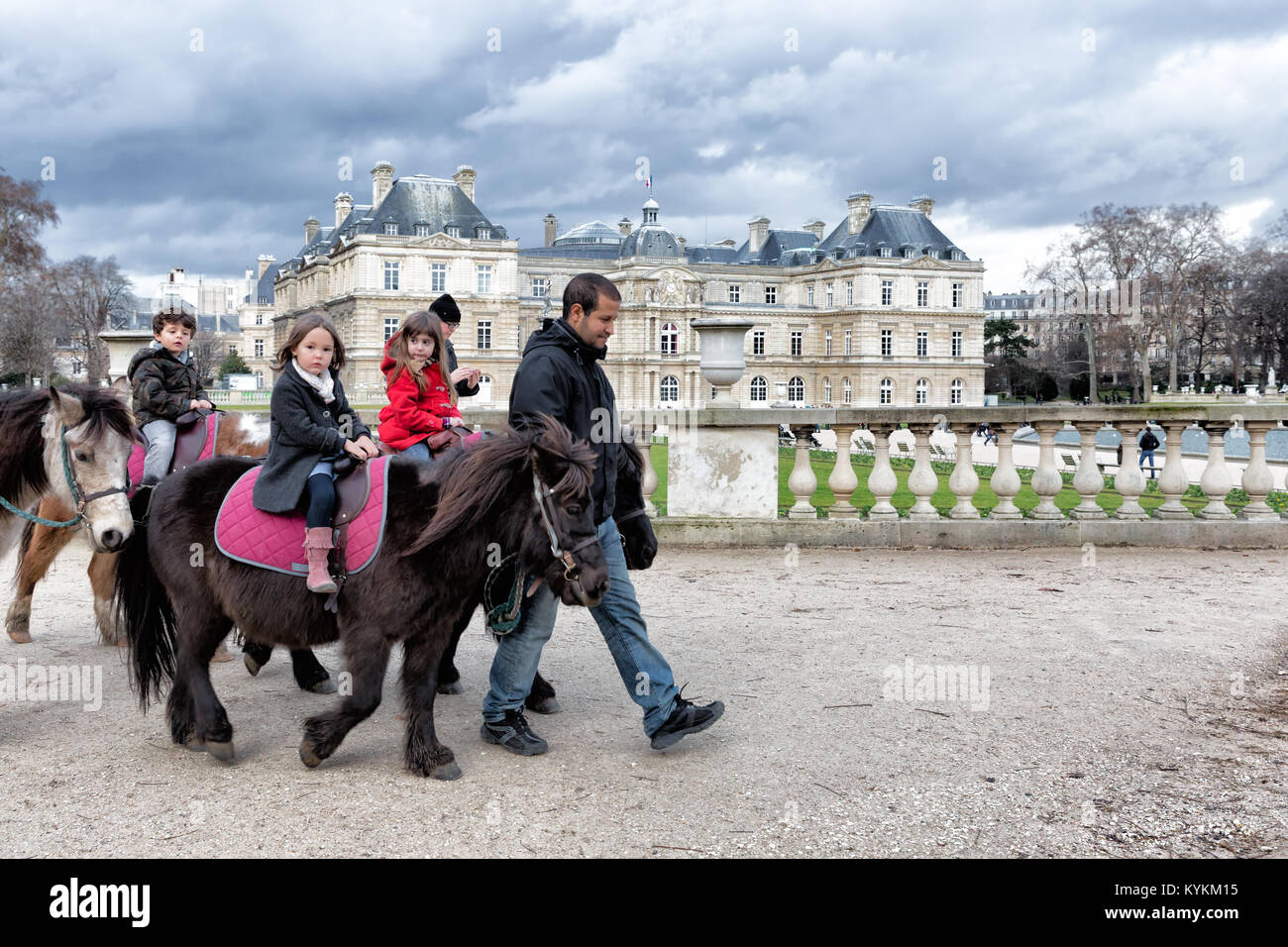 PARIS-JAN 4, 2014:Unidentified kids ride ponies at the Luxembourg Gardens, a popular activity for young visitors Stock Photo