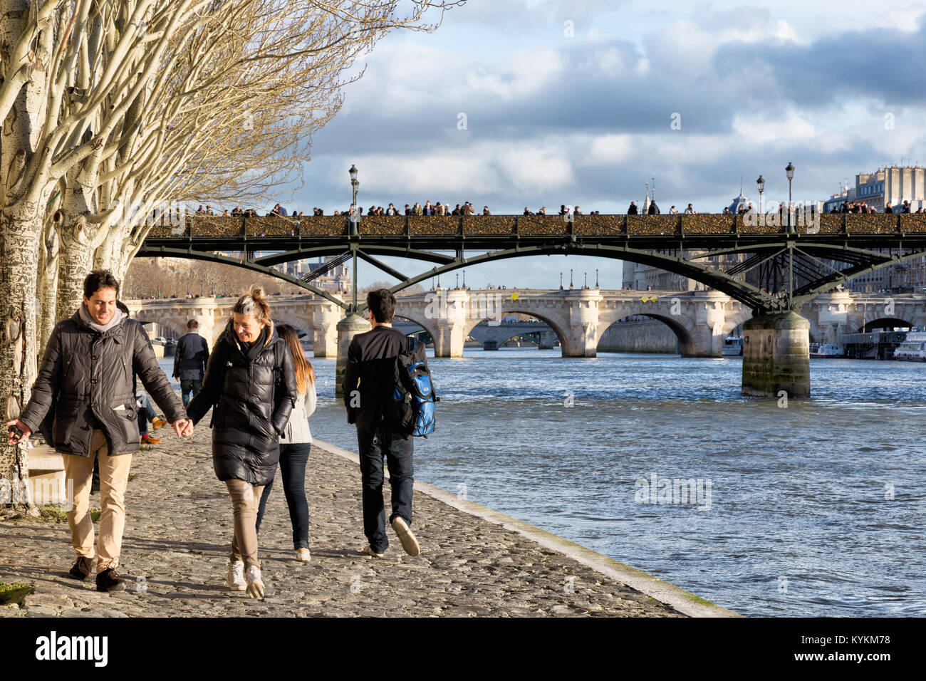 Paris, France, couples walk under old trees along the Seine River. Above is seen the famous bridge covered with Stock Photo