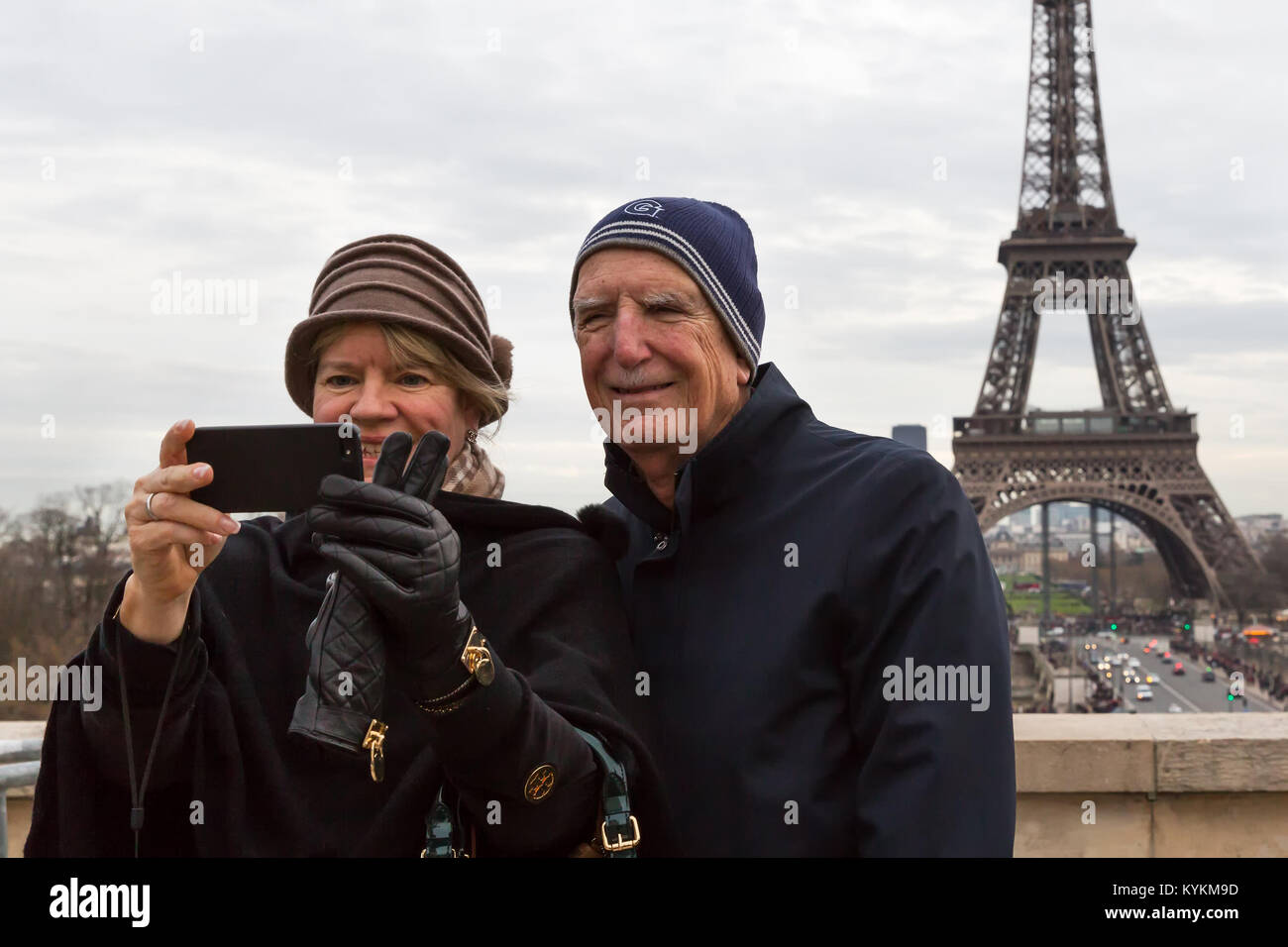 Paris France senior tourist couple take a cellphone selfie with the Eiffel Tower in the background. They smile and - Stock Image