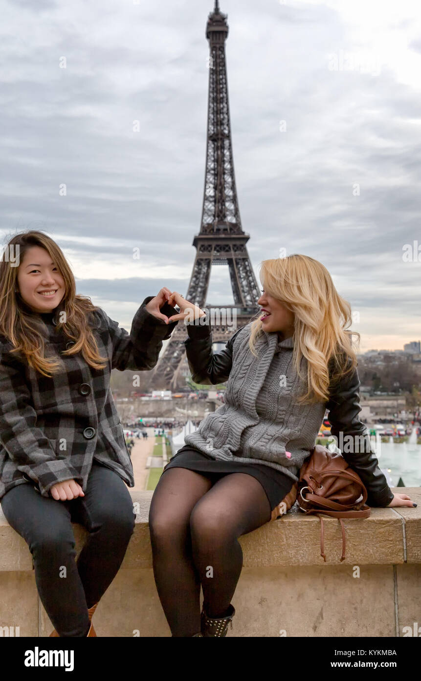 Paris Eiffel Tower tourists pose for pictures with the tower in the background. Two smiling young women make a heart - Stock Image