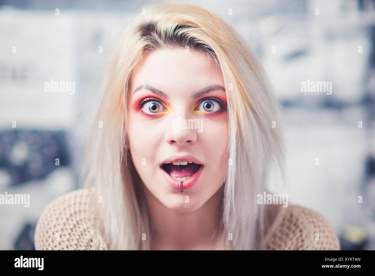 Blond young woman shocked expression red makeup - Stock Image