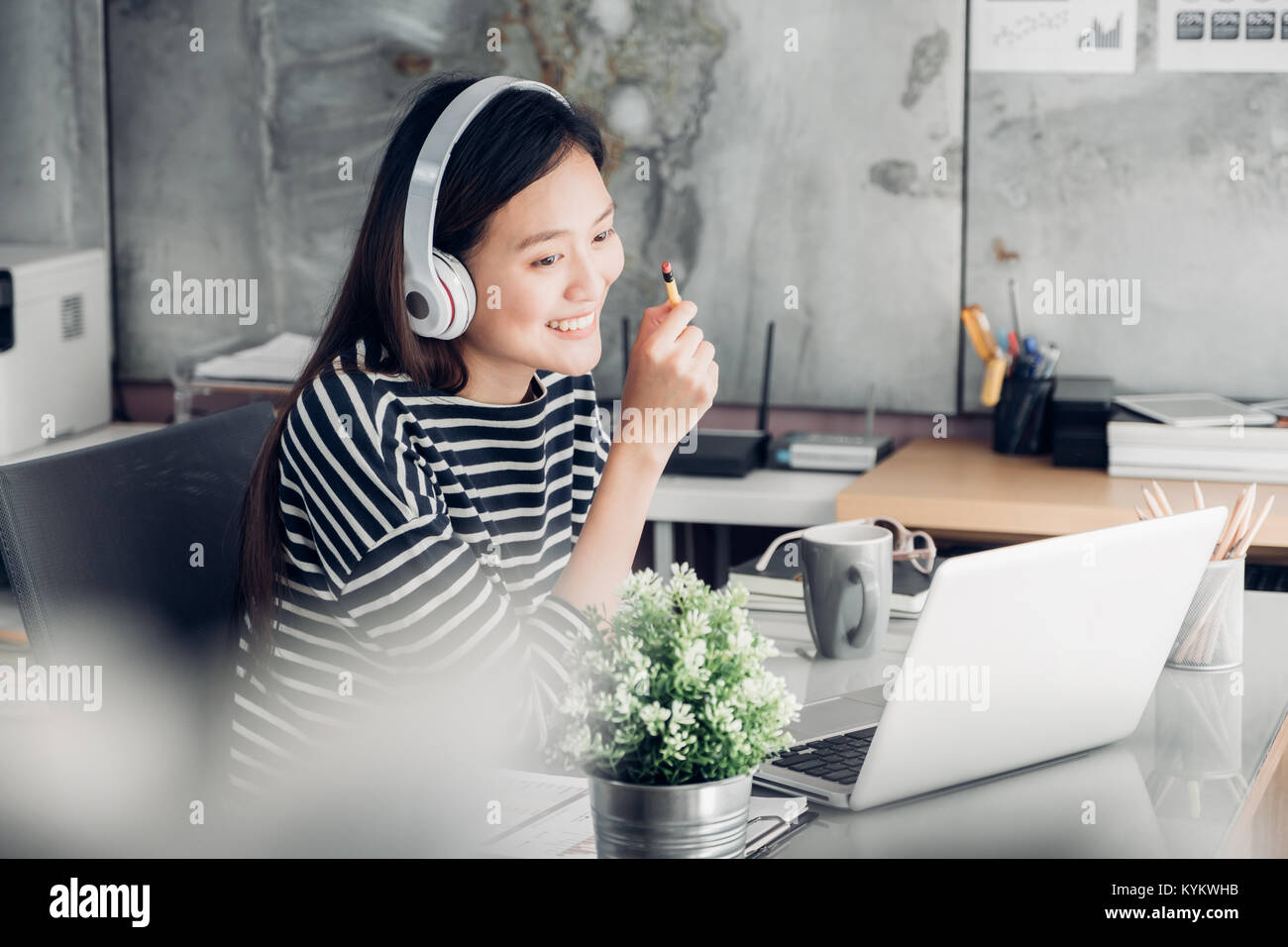 Young asian casual businesswoman arm on desk rest pose with laptop computer and listening music via headphone and - Stock Image