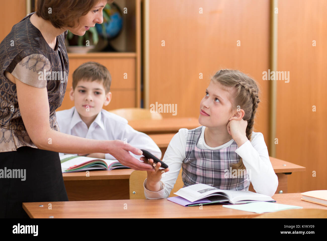 Female teacher confiscating schoolkid's mobile phone at lesson - Stock Image