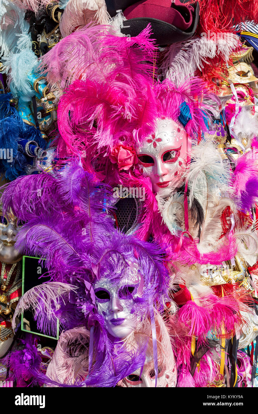 Ornate carnival masks among colorful feathers in Venice, Italy. - Stock Image