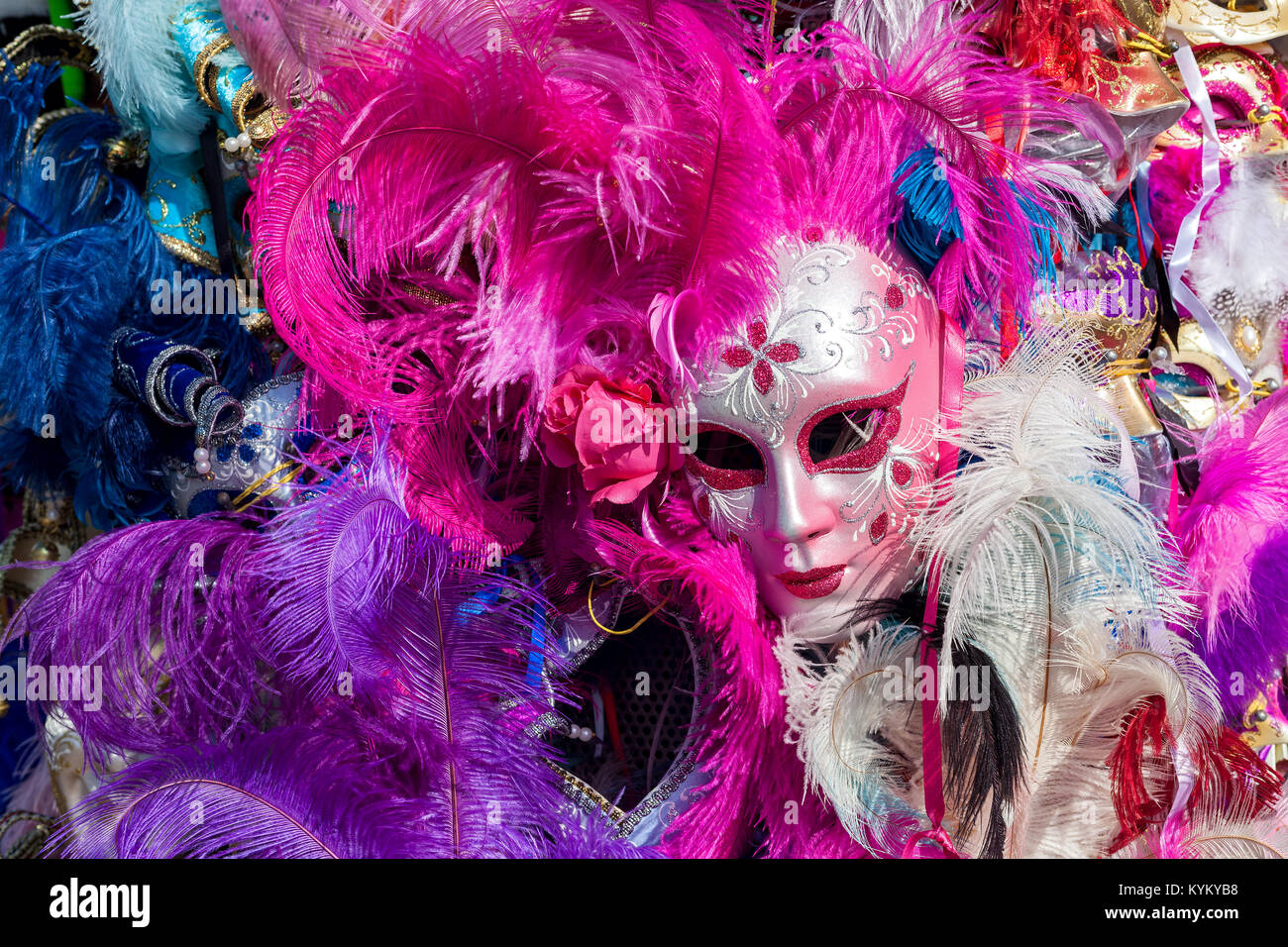 Ornate carnival mask among colorful feathers in Venice, Italy. - Stock Image