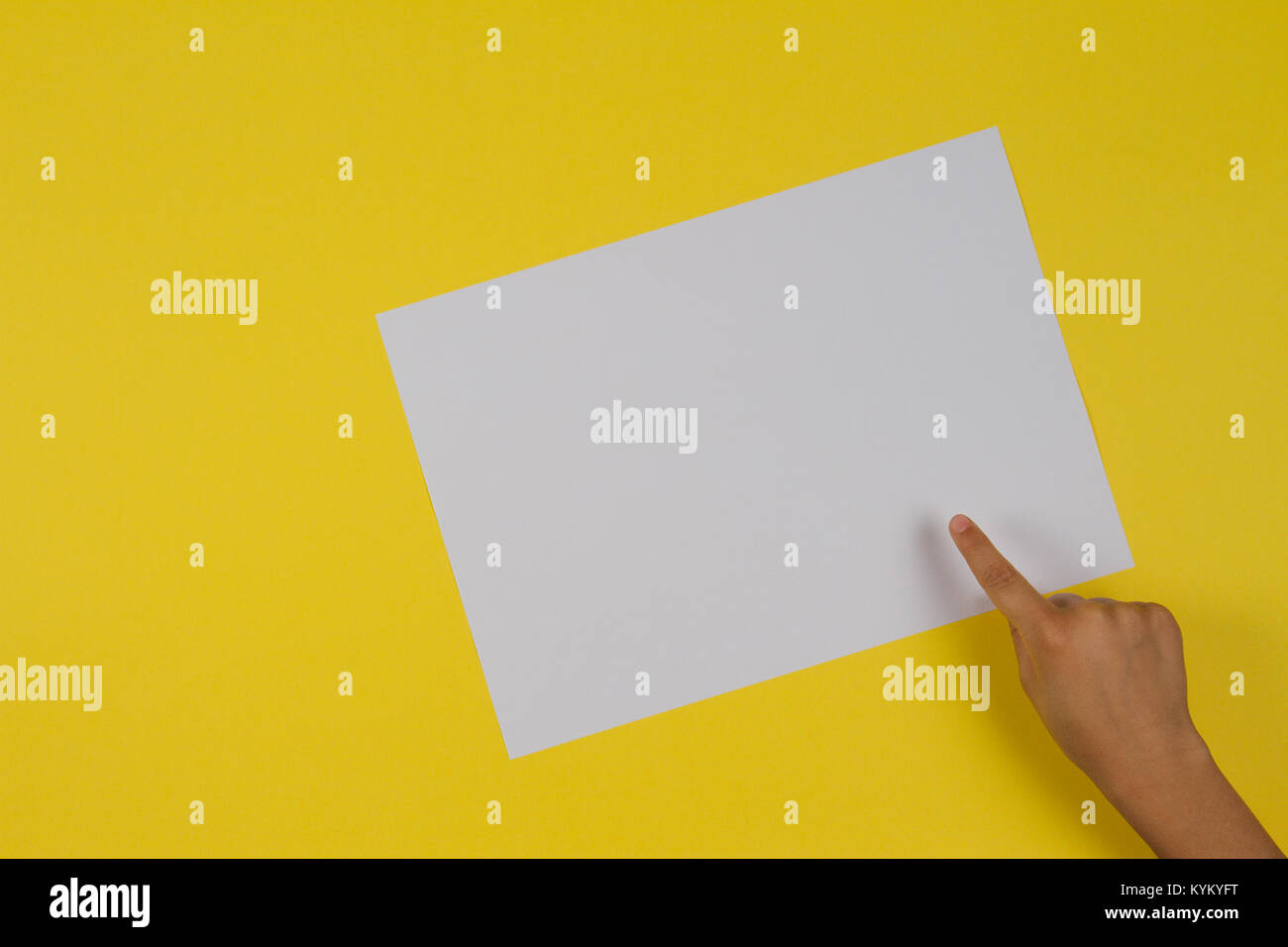 Kids hand finger pointing to white blank paper card on yellow background. - Stock Image