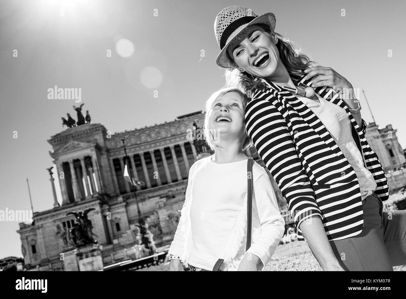 Roman Holiday. happy trendy mother and child travellers at Piazza Venezia in Rome, Italy looking at each other - Stock Image