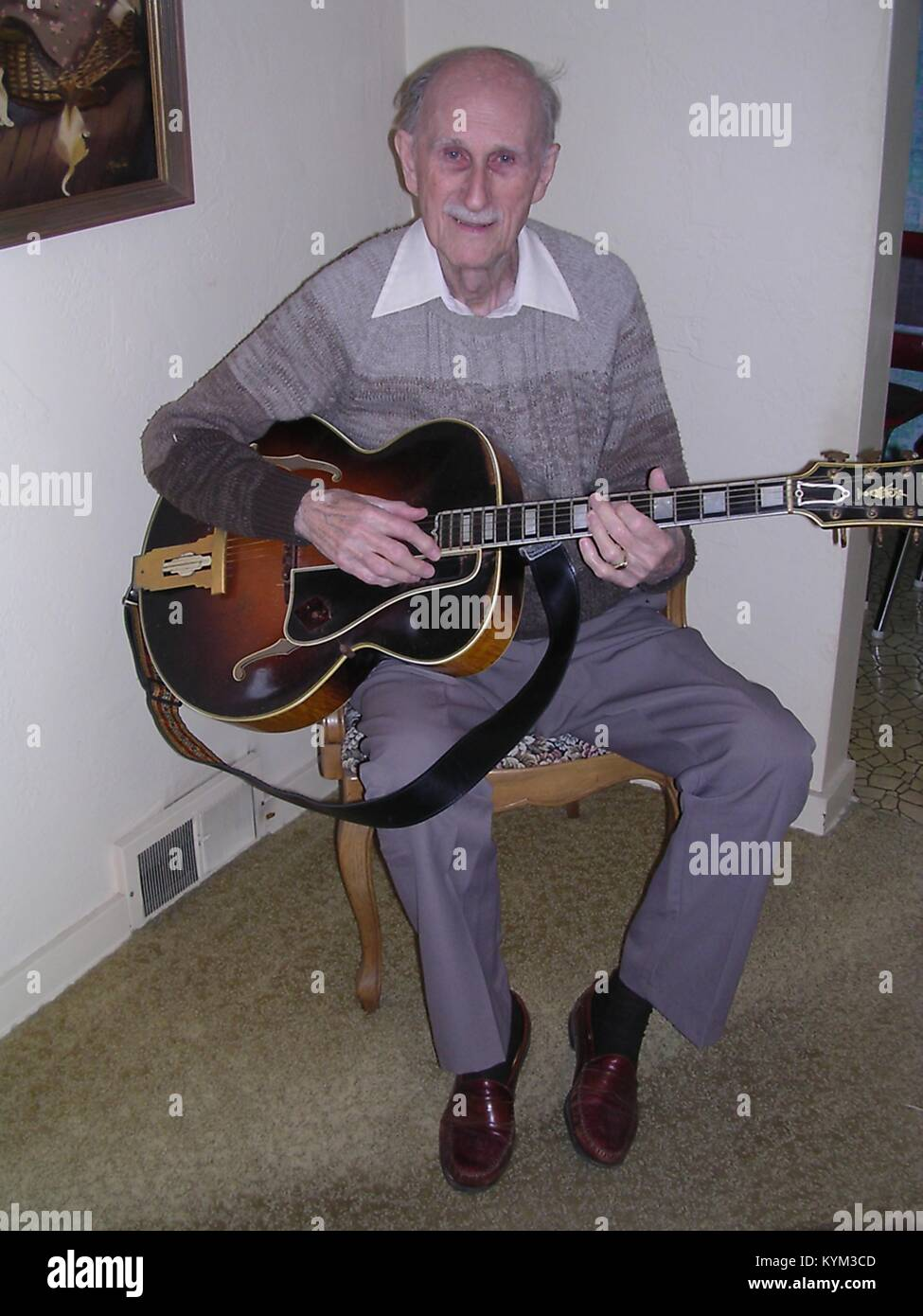 Full length seated portrait of Slim Bryant, who was the last living musician to play with the country music legend - Stock Image