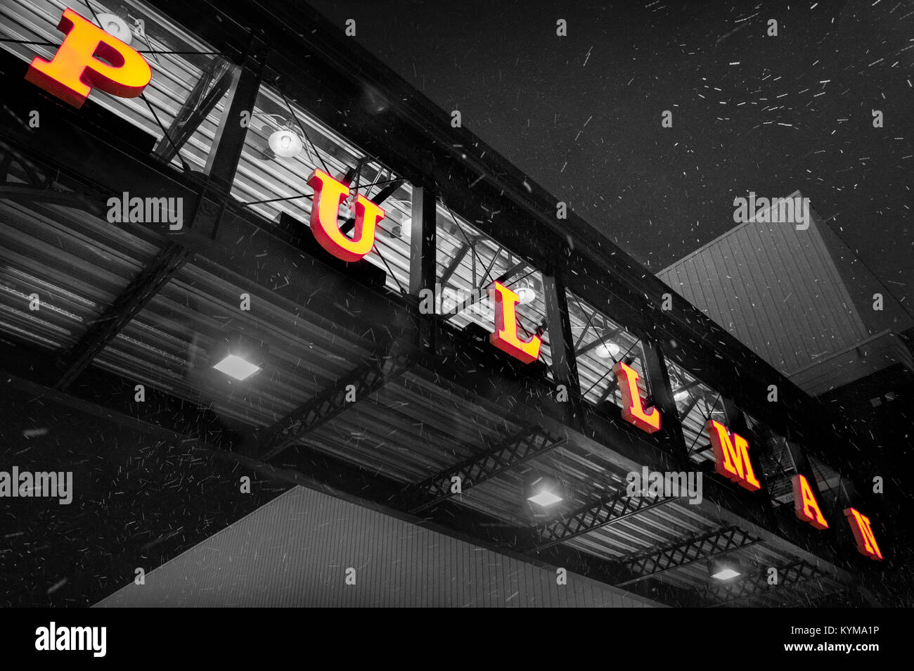 A large neon sign adorns the walkway connecting the parking garage with Pullman Square as snow fills the air in - Stock Image
