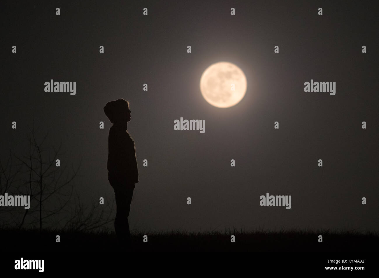 A profile view of a girl wearing a hoodie stands silhouetted surrounded by darkness under a full moon looking to - Stock Image