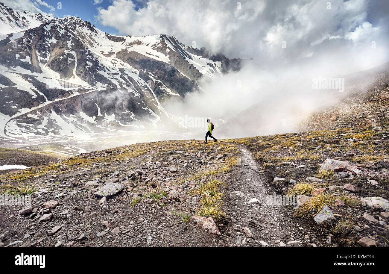 Hiker in green shirt with backpack walking in the snowy mountains at foggy sky background - Stock Image