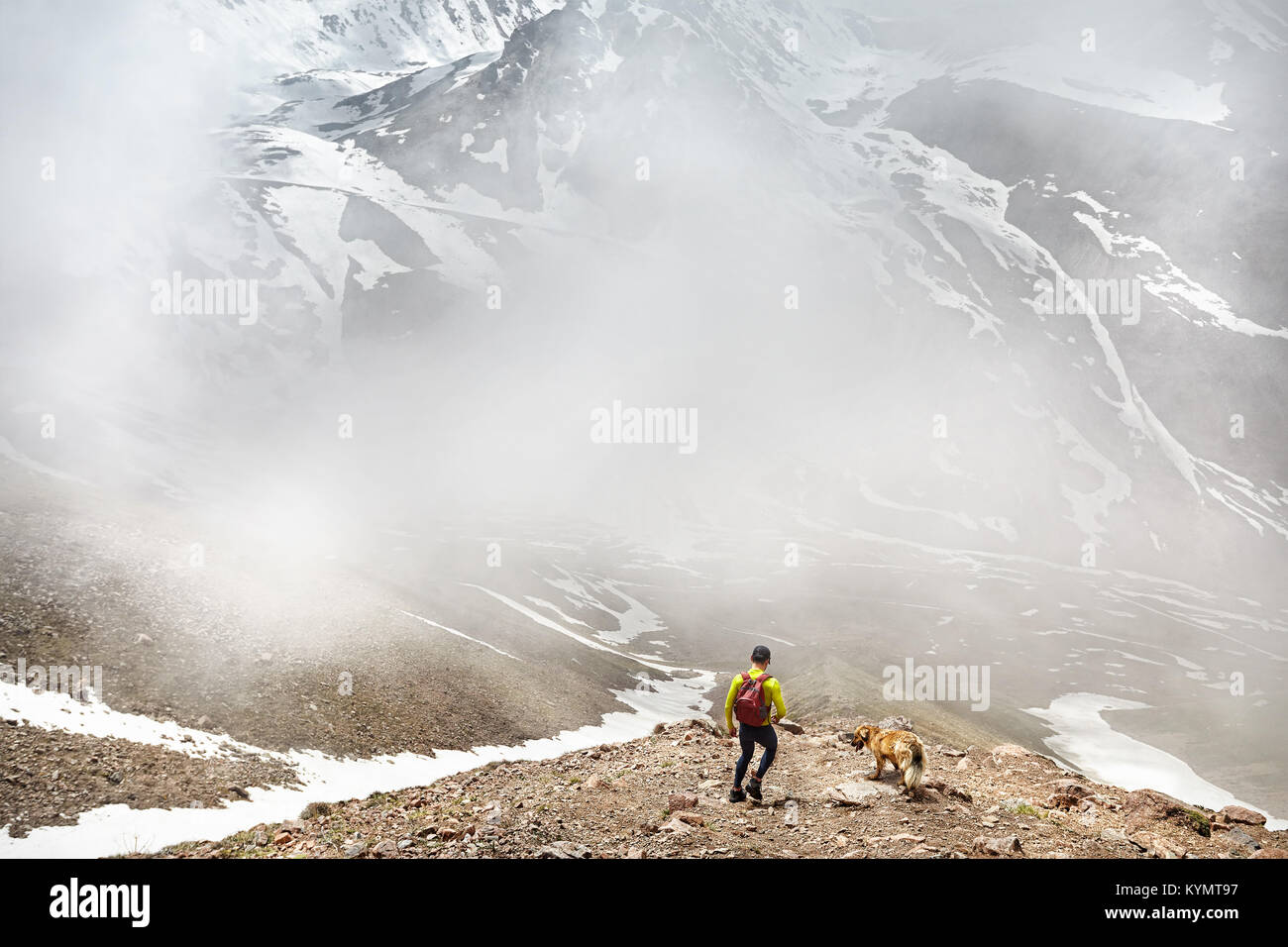 Hiker in green shirt with backpack and dog walking in the snowy mountains at foggy sky background - Stock Image
