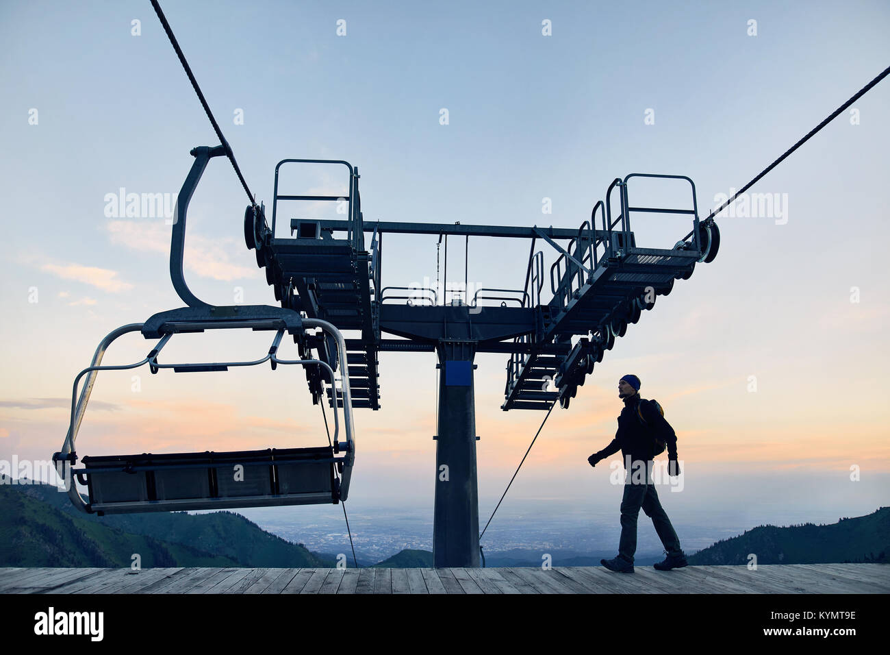 Tourist man walking at ski lift station in silhouette high in mountain ski resort at sunrise - Stock Image