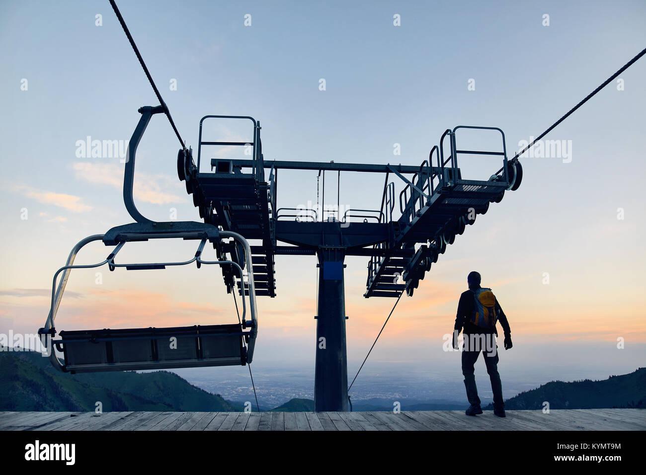 Tourist man walking at ski lift station in silhouette high in mountain ski resort at sunrise - Stock Image