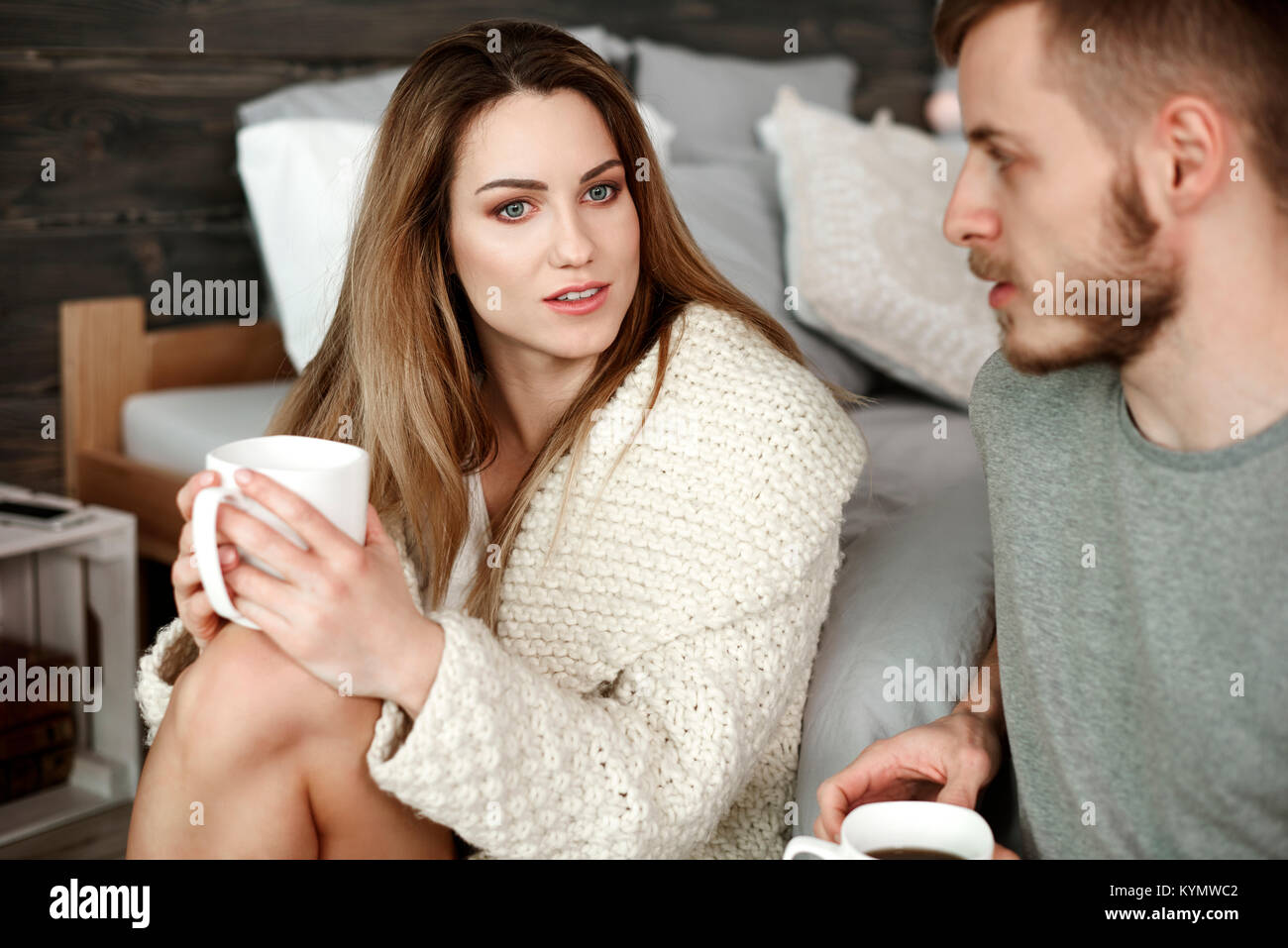 Couple with coffee arguing at bedroom - Stock Image