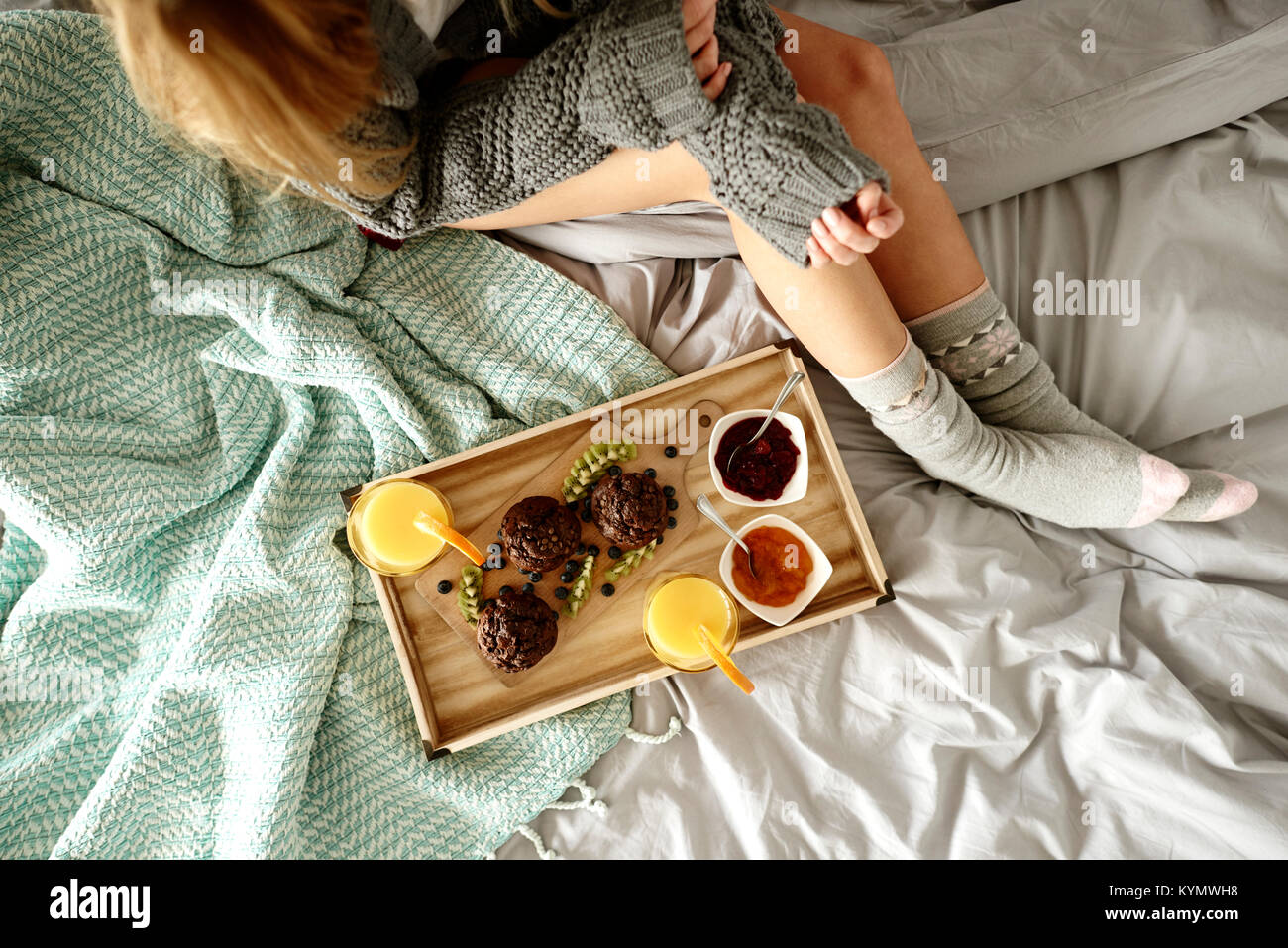 Unrecognizable woman and breakfast on bed - Stock Image