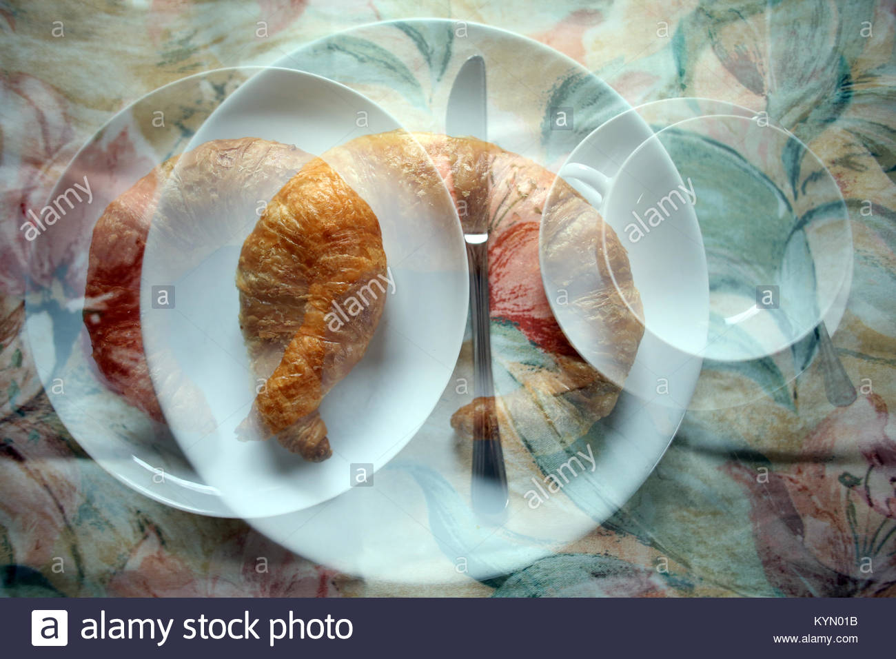 A flaky Bamberg croissant on a white plate beside a cup of coffee in German kitchen at breakfast time - Stock Image