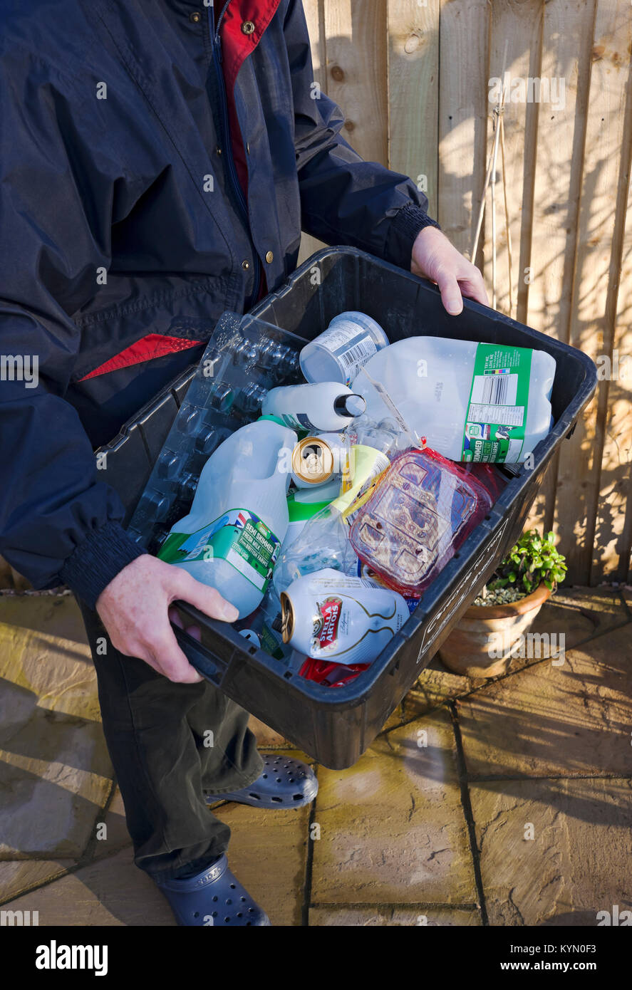 Man putting out plastic and tins recycling box for collection England UK United Kingdom GB Great Britain Stock Photo