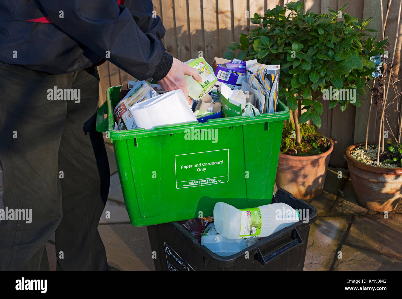 Man sorting paper card and plastics recycling boxes for collection England UK United Kingdom GB Great Britain - Stock Image