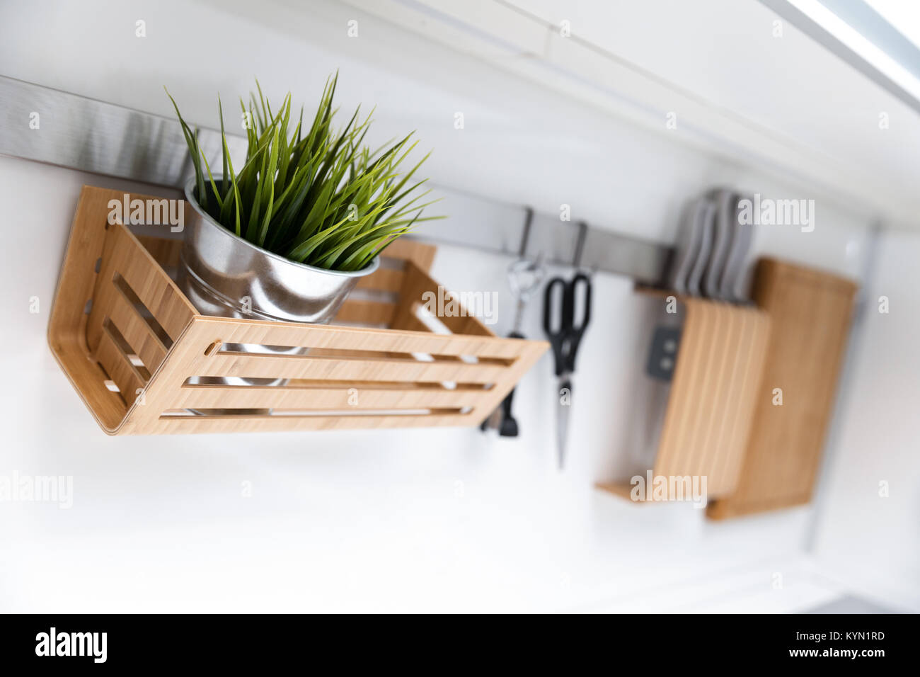 kitchen utensils and decor hanging on the white wall - Stock Image