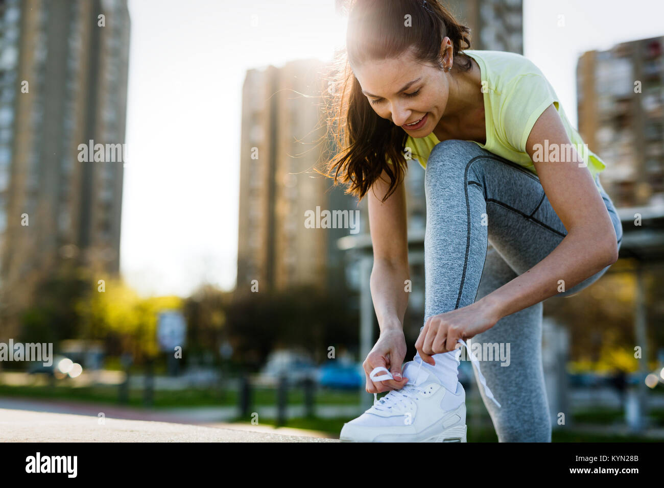 Attractive sportswoman tying shoelace and getting ready for fitness Stock Photo