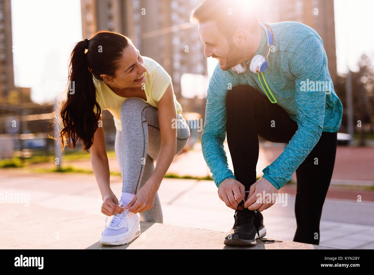 Runners tying running shoes and getting ready to run - Stock Image