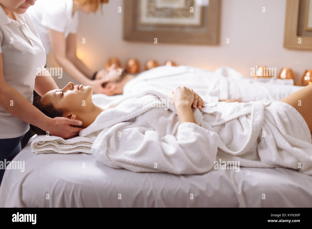 happy young beautiful couple enjoying head massage at the spa - Stock Image