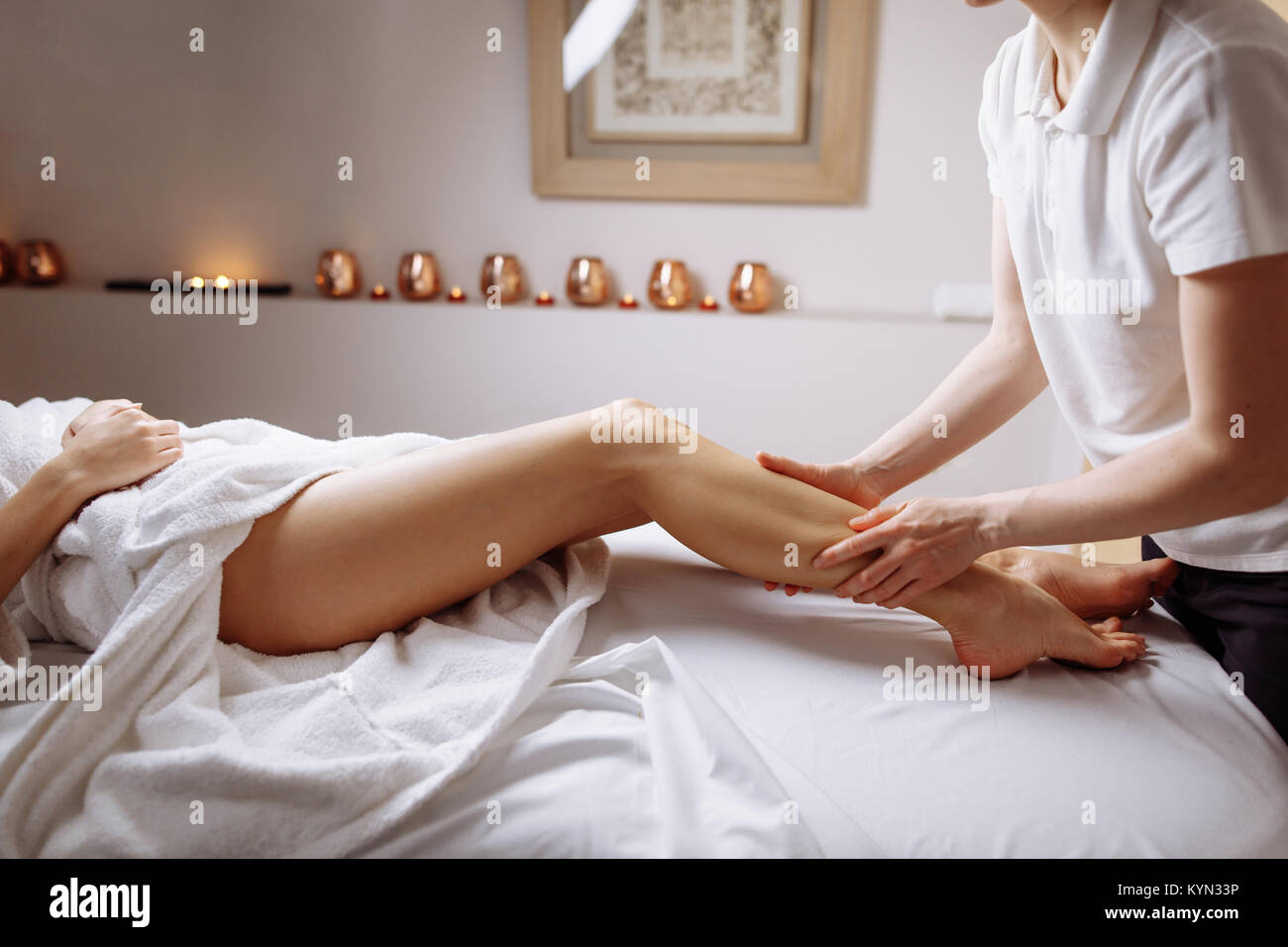 hands massaging human calf muscle.Therapist applying pressure on leg - Stock Image