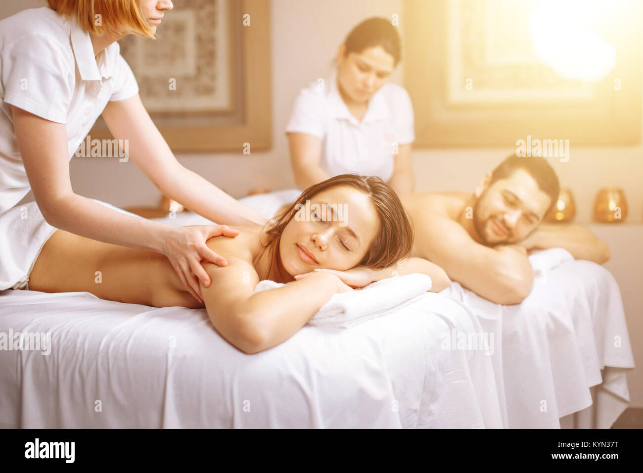 Happy couple getting massage at spa - Stock Image