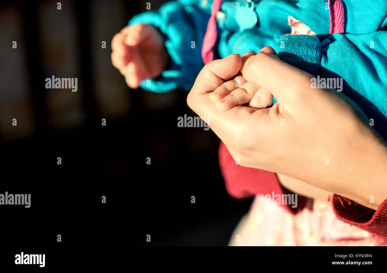 Caucasian woman's hands holding the hand of her white baby in natural sunlight with defocused background and copy Stock Photo