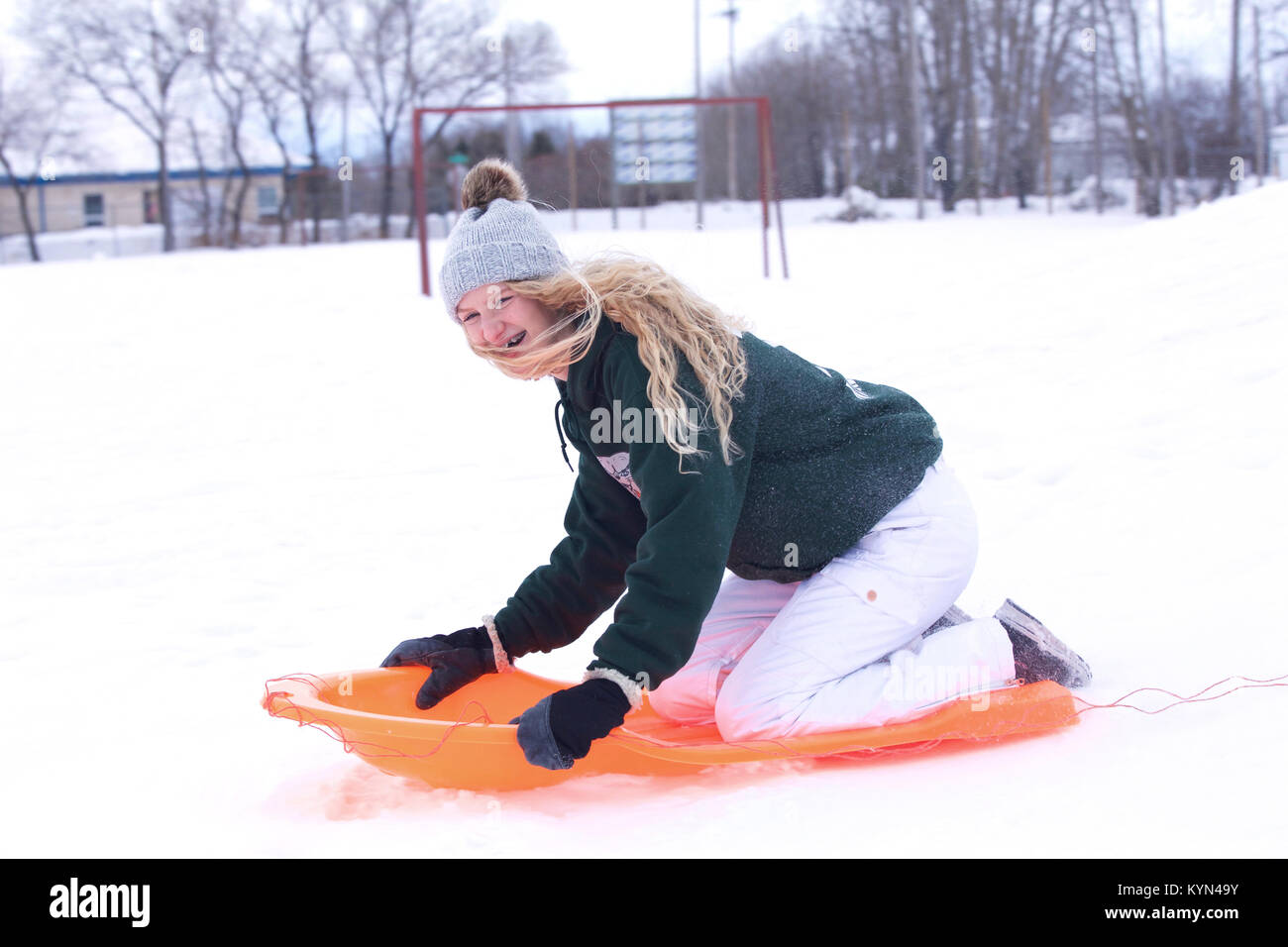 A laughing teenaged girl in ski pants and snow hat over her long hair sliding down a hill on a toboggan in a winter - Stock Image