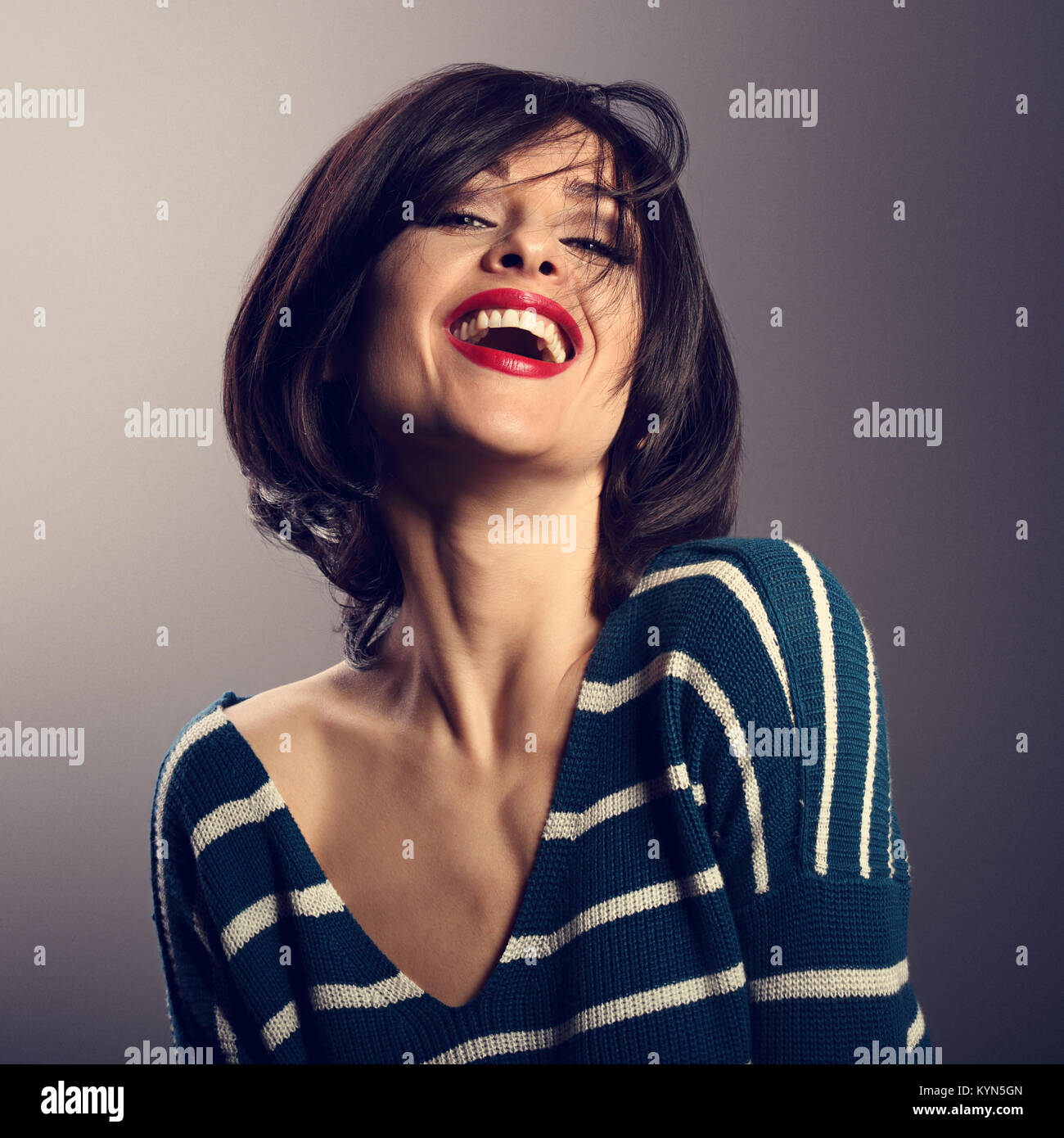 Happy loudly laughing with wide open mouth young woman with short hair in fashion sweater. portrait - Stock Image