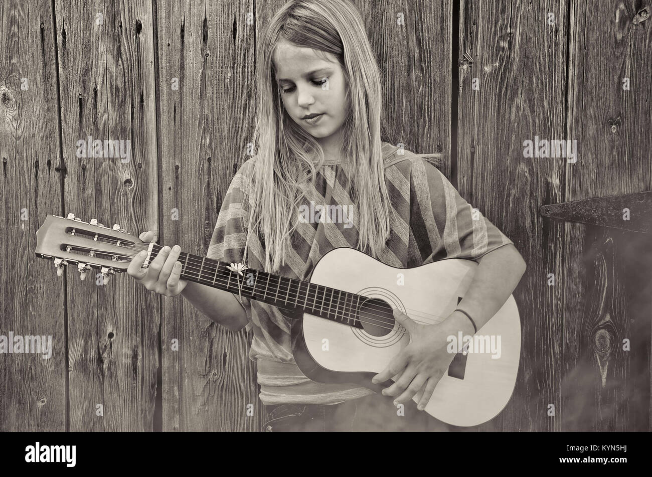 young girl playing guitar by old rustic wooden barn with fog in sepia tones - Stock Image