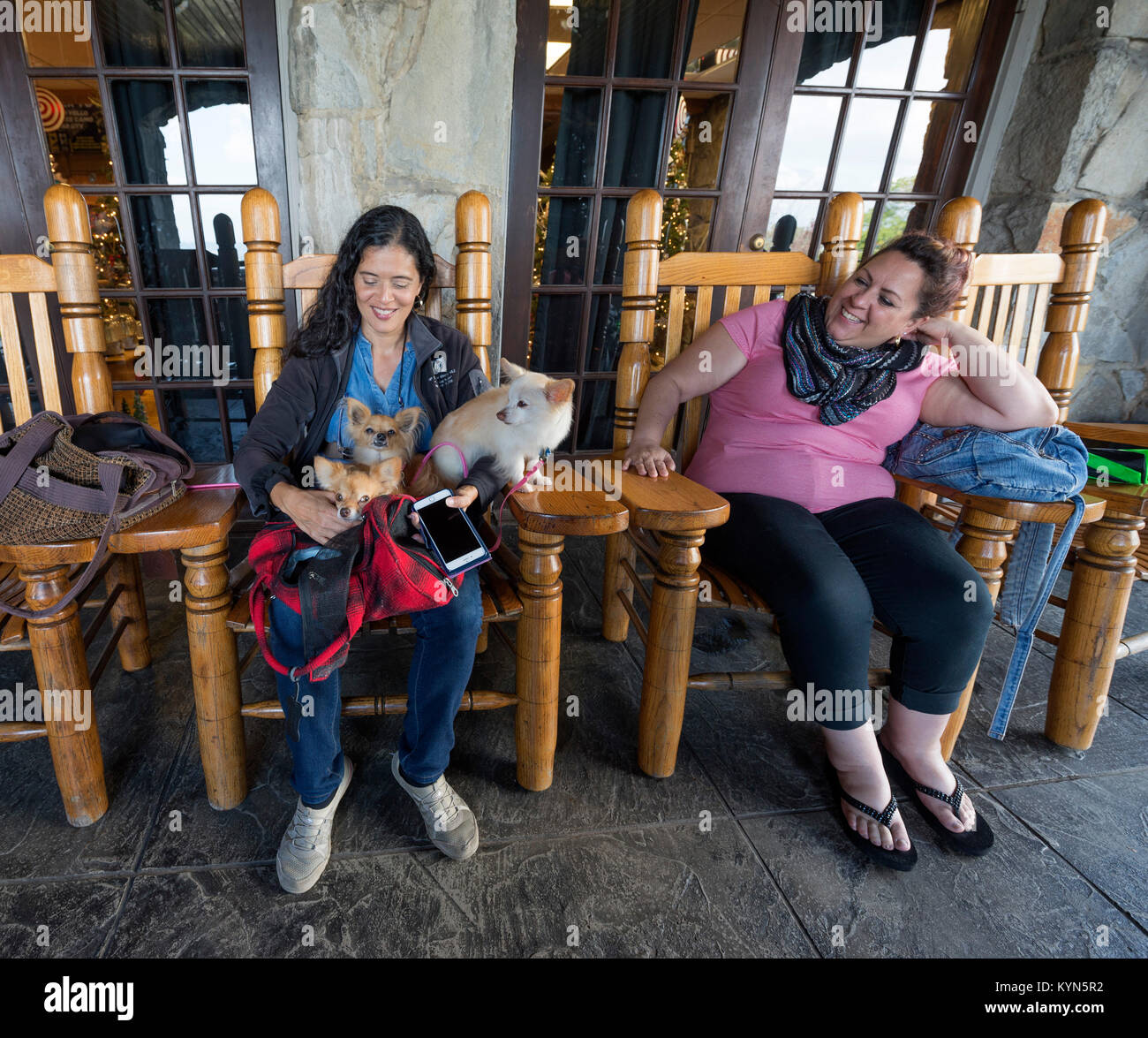 Women watching dogs while their families tour Ruby Falls in Chattanooga, Tennessee. - Stock Image