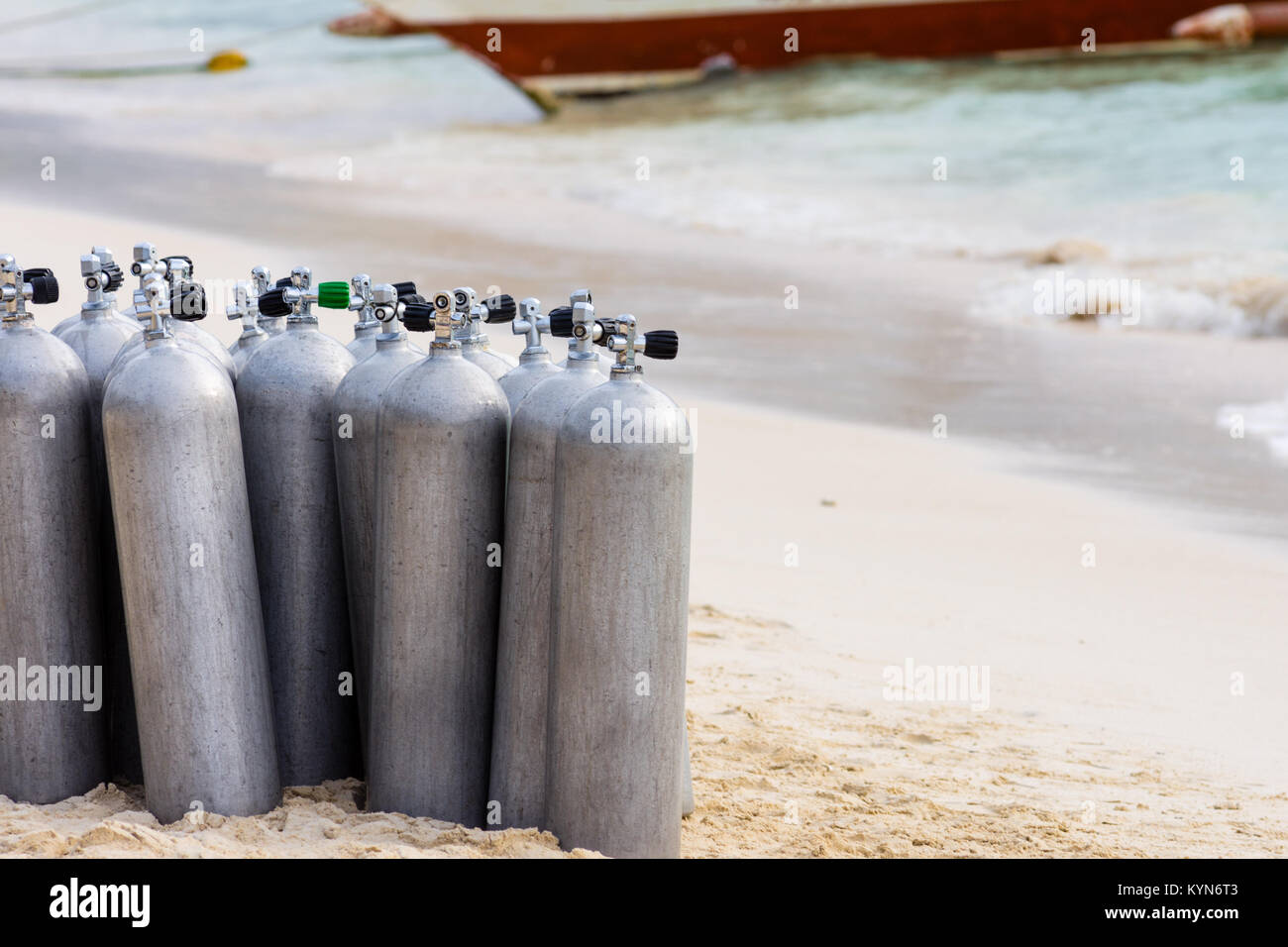 A collection of scuba divers air taks on a tropical white sand beach. - Stock Image