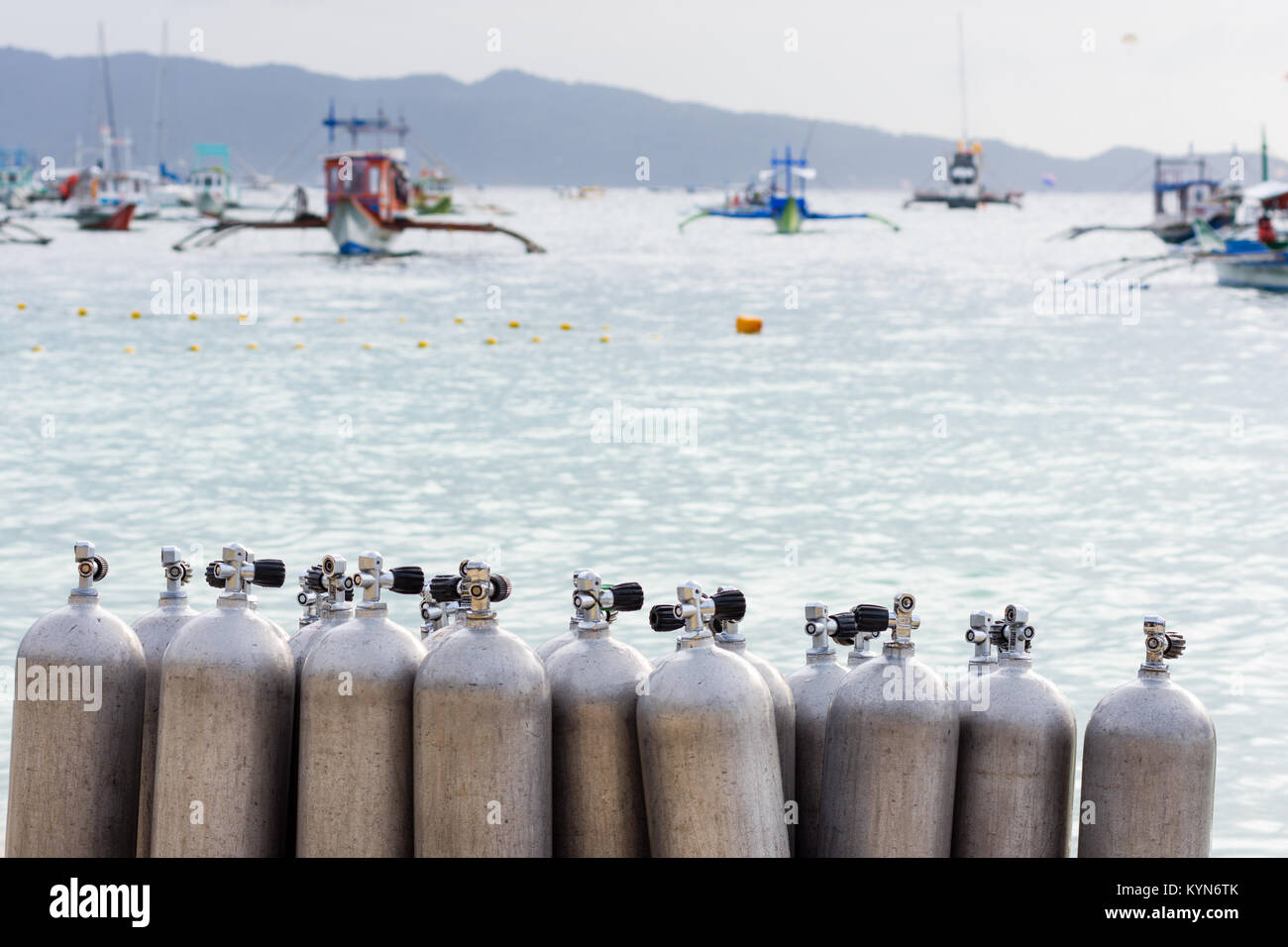 A collection of scuba divers air taks on a tropical white sand beach with depth of field back ground of calm sea - Stock Image