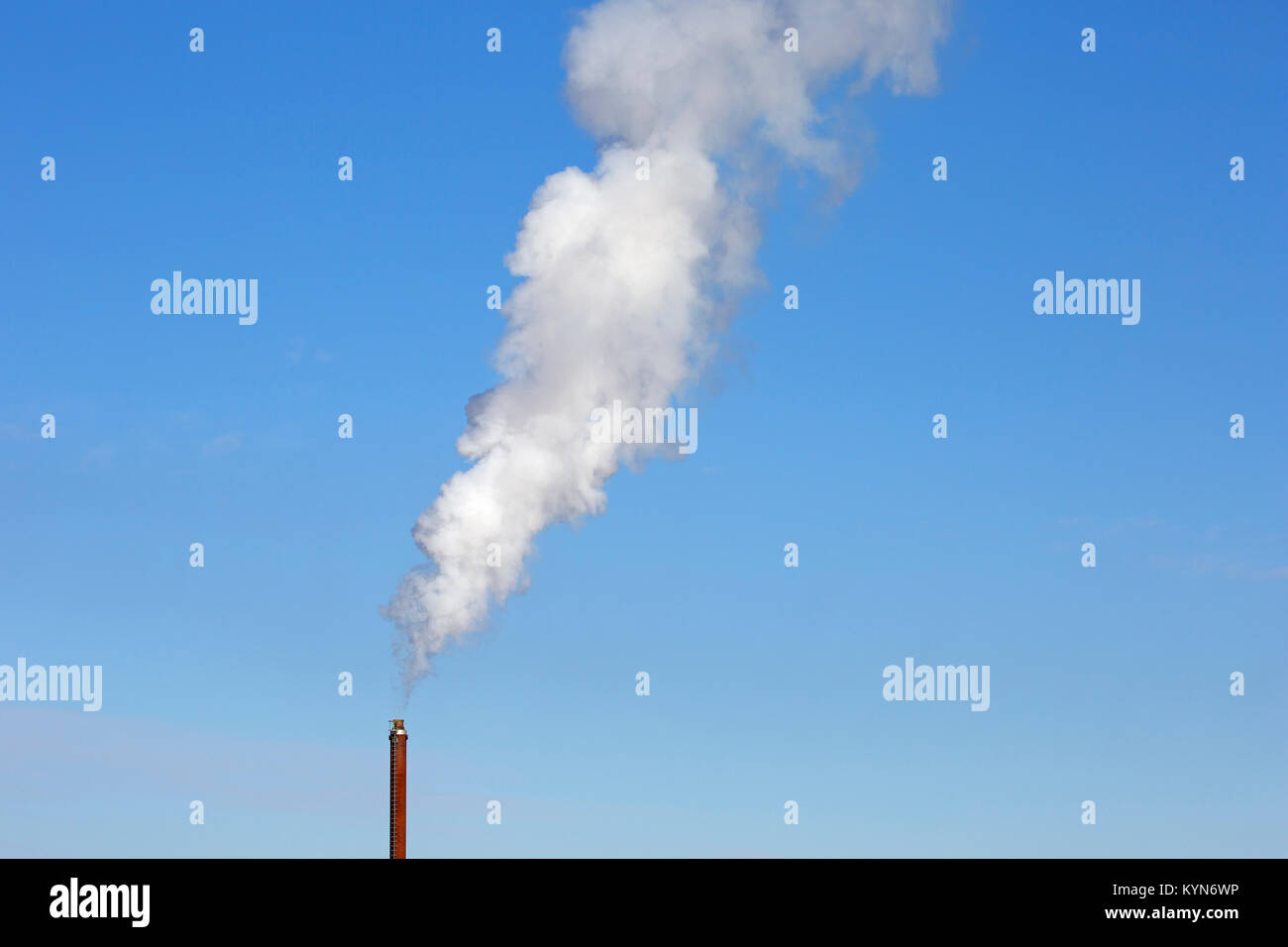 Industrial chimney / smoke stack / smokestack against blue sky on a windless day - Stock Image