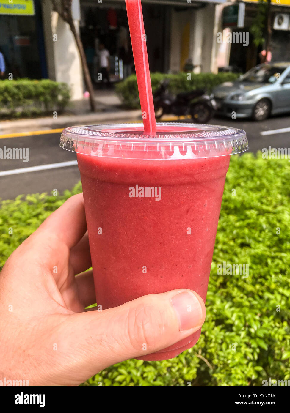A male human hand holding up a clear plastic cup of a cold Strawberry Smoothie with a red straw and city street - Stock Image