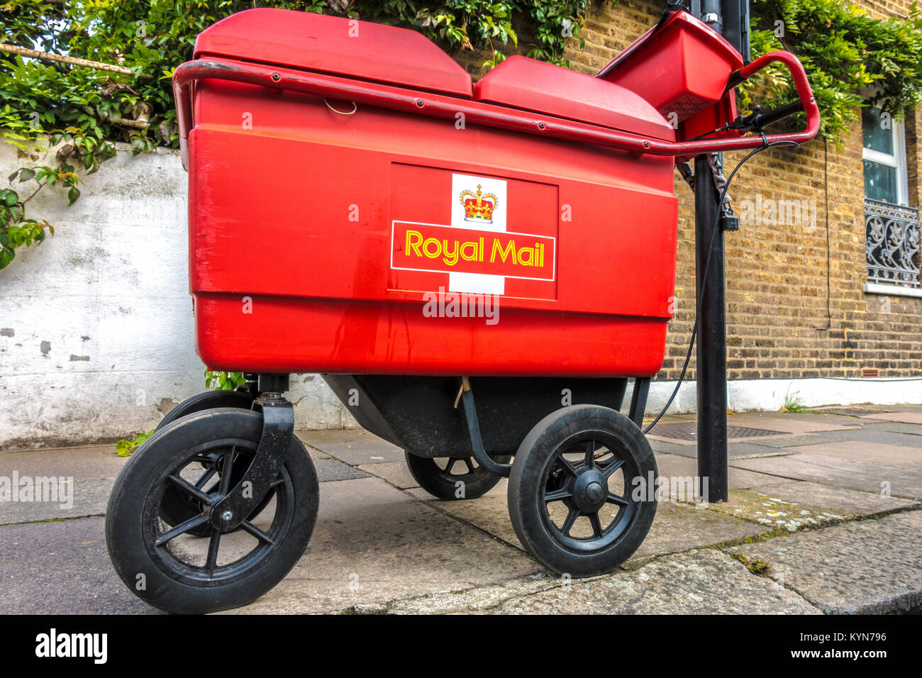 Royal Mail, four wheeled delivery trolley (high capacity used by postmen with parcels to deliver), chained to a - Stock Image