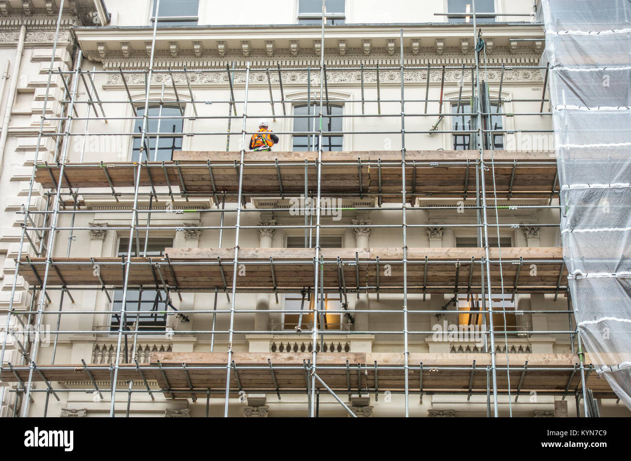 Workman in hard hard and safety clothing, standing on a scaffolding platform, outside a multi storey property. South - Stock Image