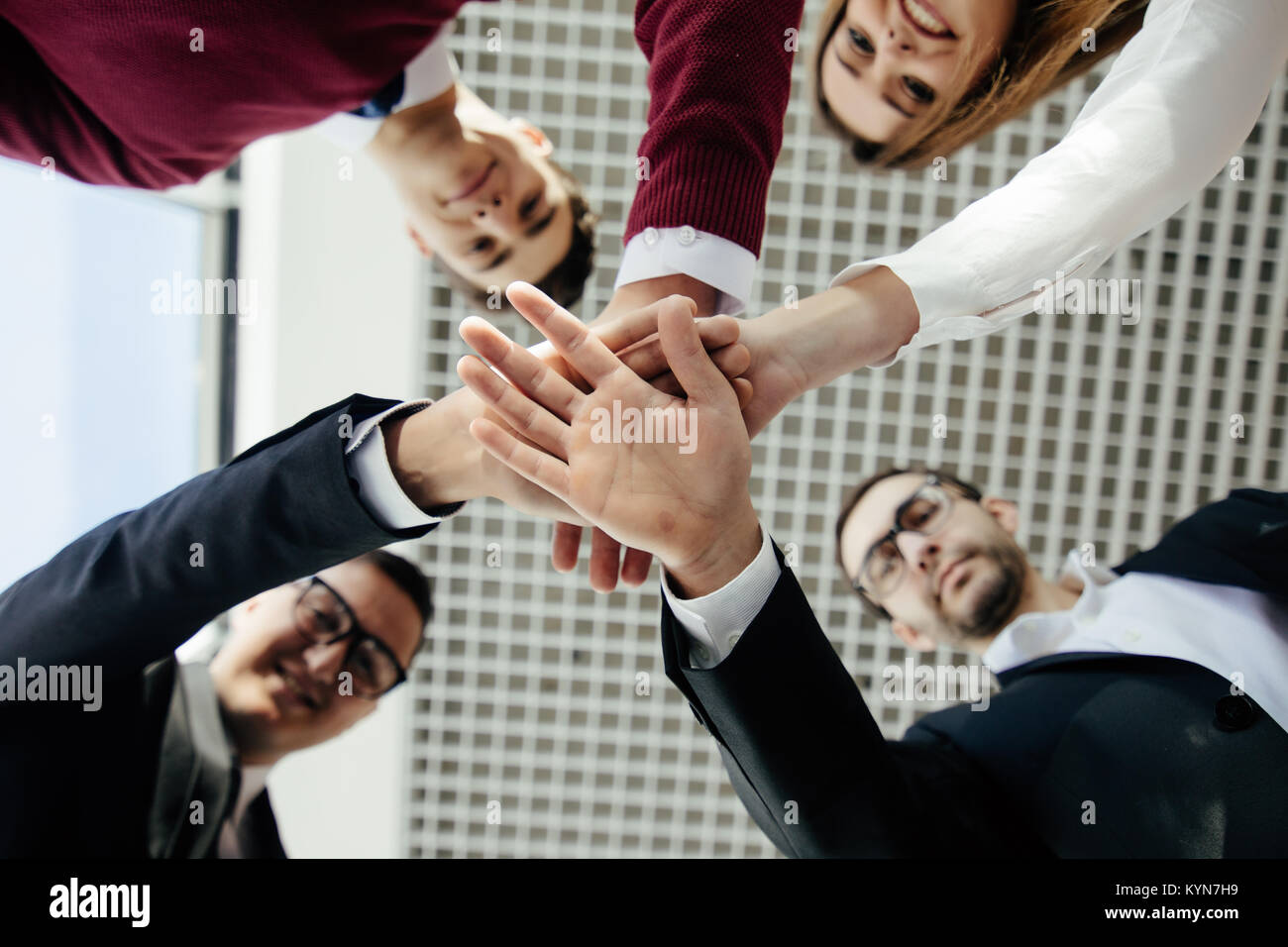 Close-up of business partners making pile of hands at meeting - Stock Image