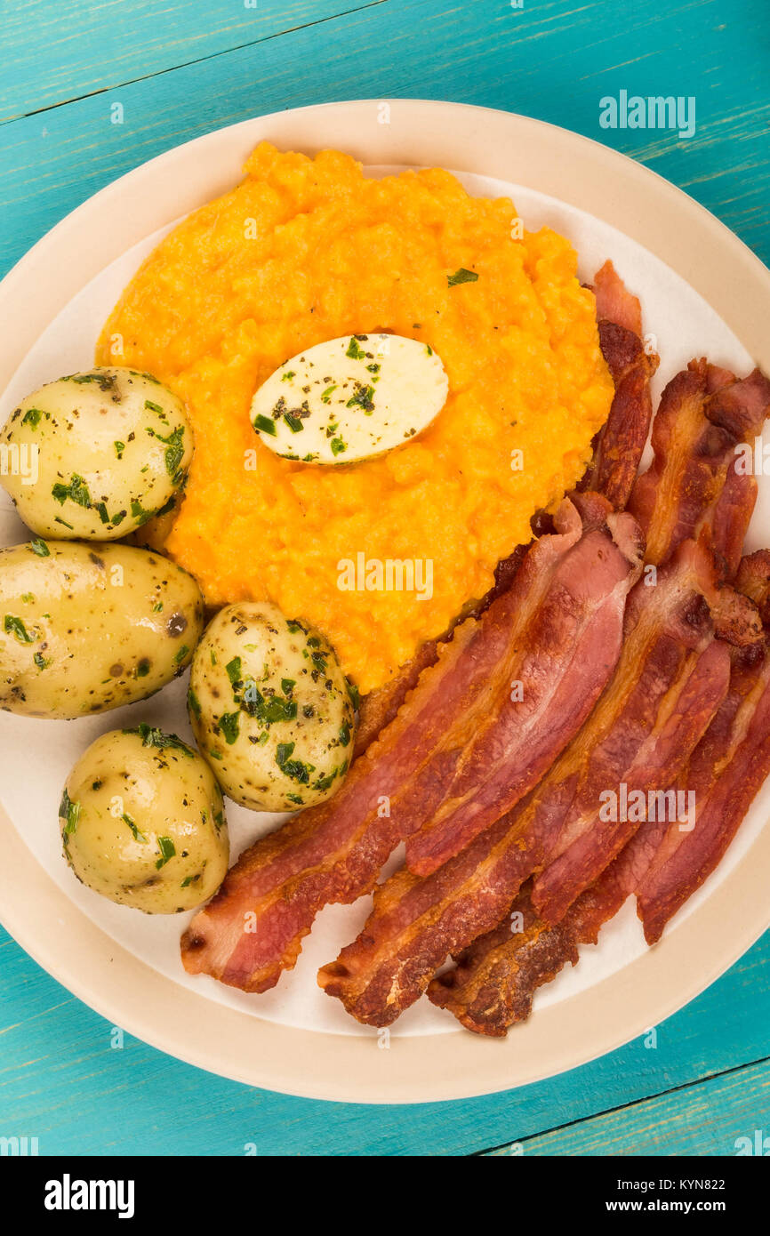 Norwegian Pork or Crispy Bacon With Mashed Swede and Boiled Potatoes Meal Against a Blue Background - Stock Image