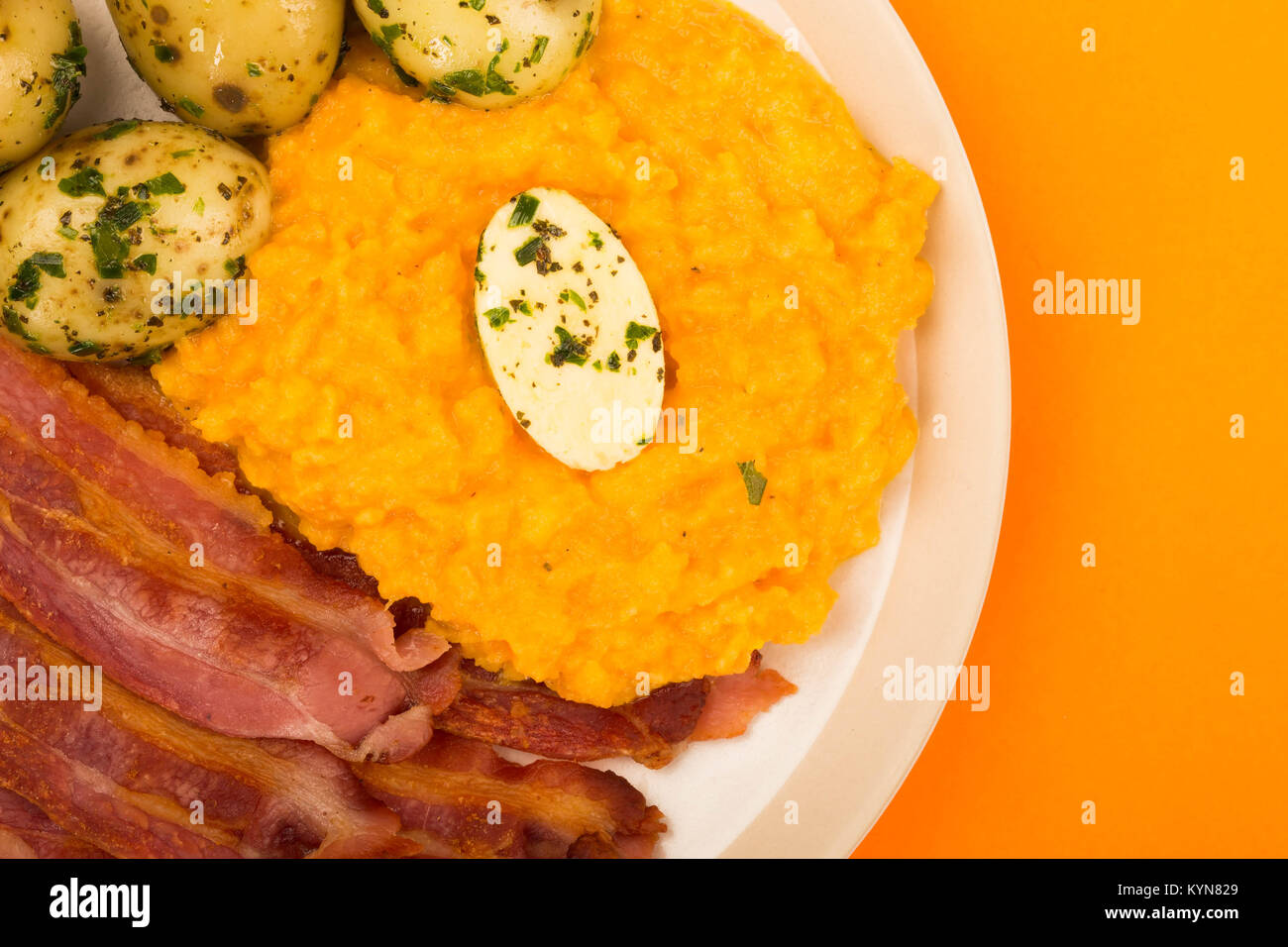 Norwegian Pork or Crispy Bacon With Mashed Swede and Boiled Potatoes Meal Against an Orange Background - Stock Image