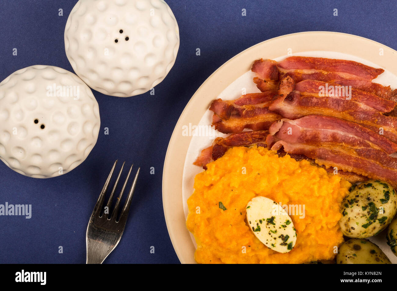 Norwegian Pork or Crispy Bacon With Mashed Swede and Boiled Potatoes Meal Against a Purple Background - Stock Image