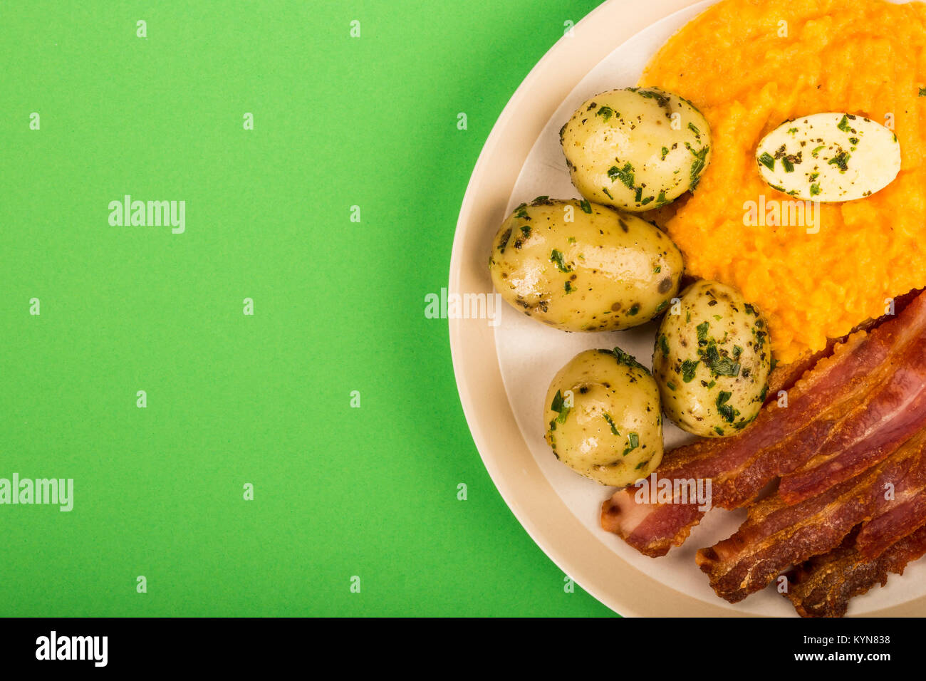 Norwegian Pork or Crispy Bacon With Mashed Swede and Boiled Potatoes Meal Against A Green Background - Stock Image