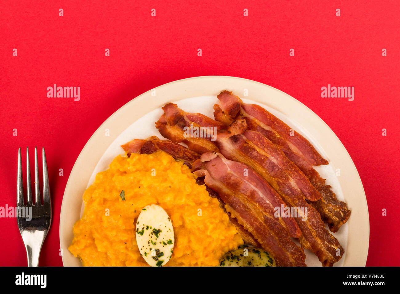 Norwegian Pork or Crispy Bacon With Mashed Swede and Boiled Potatoes Meal Against A Red Background - Stock Image